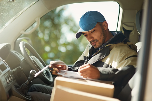 A man reading addresses while sitting in a delivery van
